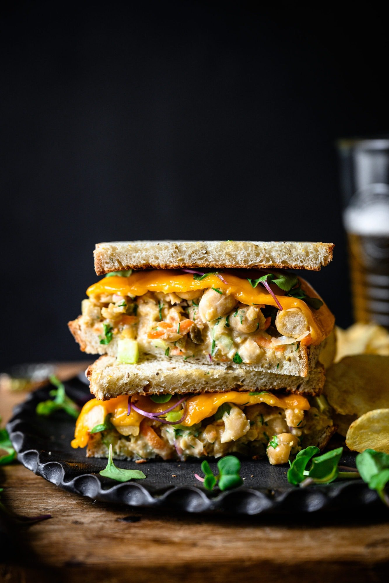 side view of a vegan tuna salad sandwich sliced in half and stacked on a plate with potato chips.