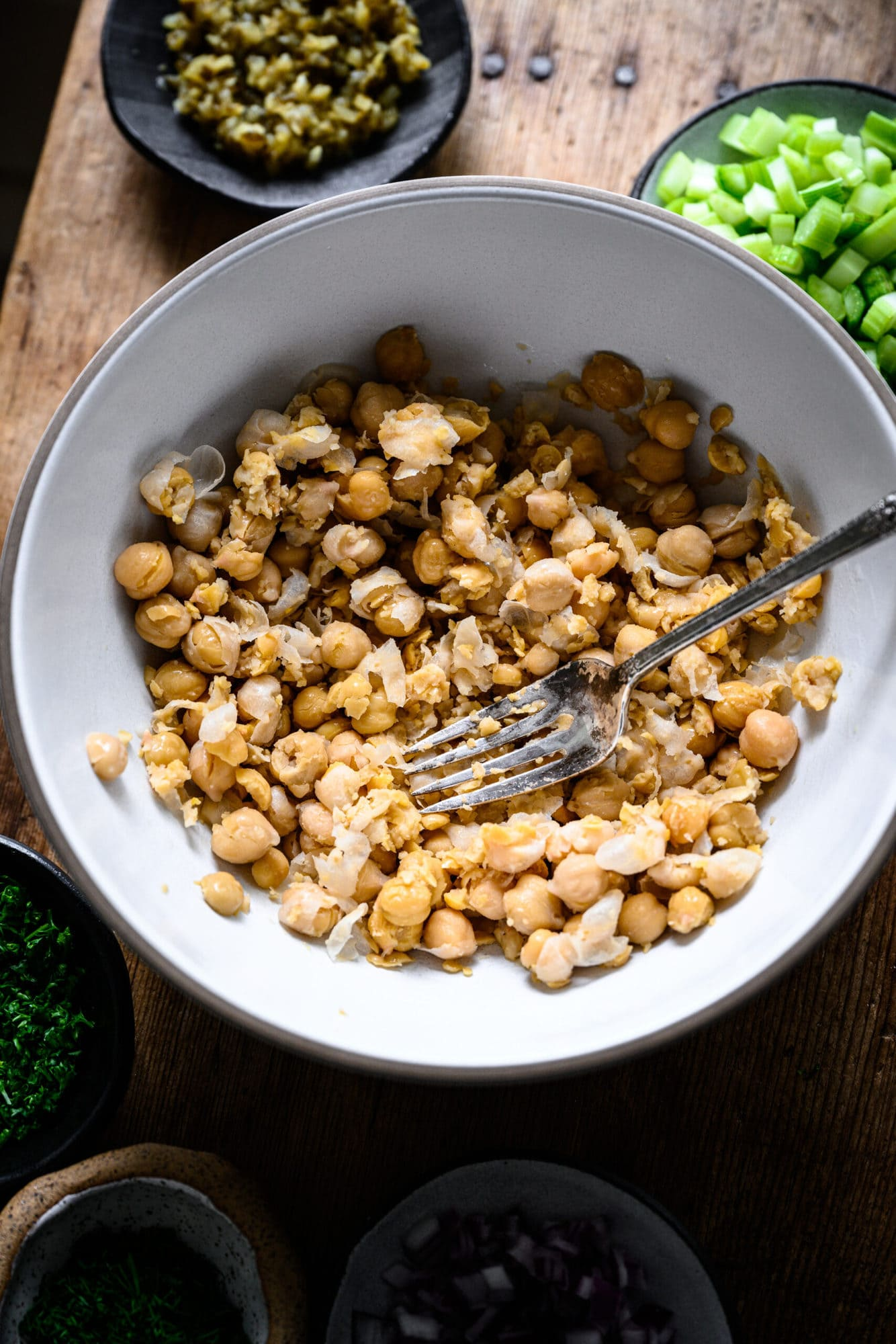 close up view of mashed chickpeas in a bowl with a fork.