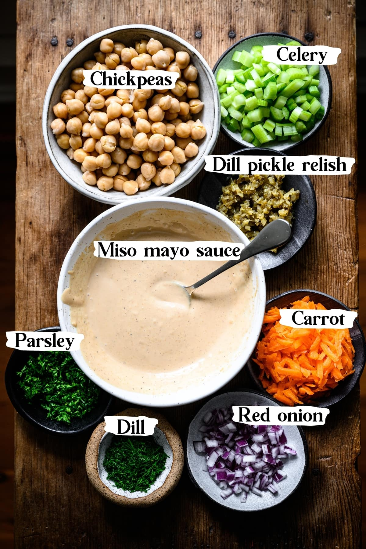 overhead view of ingredients for vegan tuna salad, including chickpeas, carrot, celery, onion, dill, parsley and miso mayo sauce.