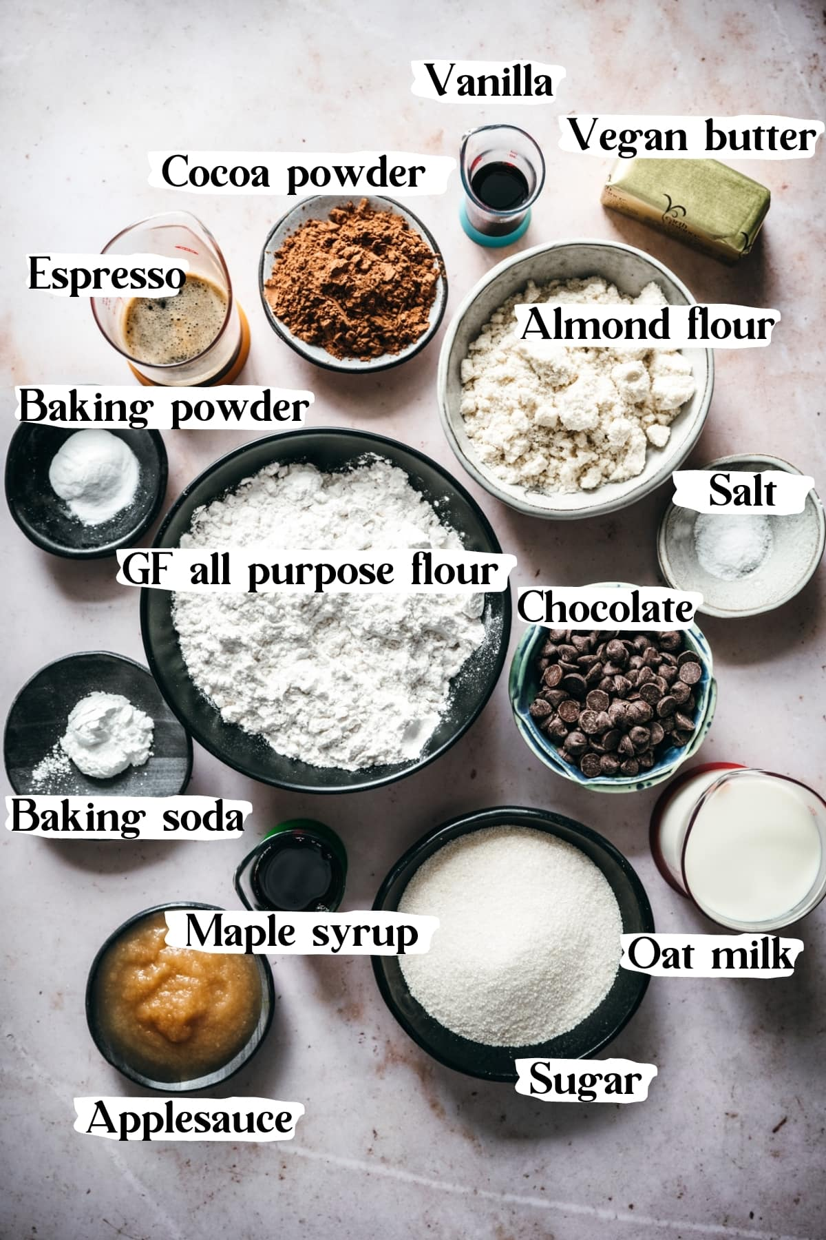 overhead view of ingredients to make vegan chocolate cake, including flour, vegan butter, applesauce, chocolate, cocoa powder.