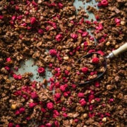 overhead view of chocolate hazelnut granola with freeze-dried raspberries on sheet pan.
