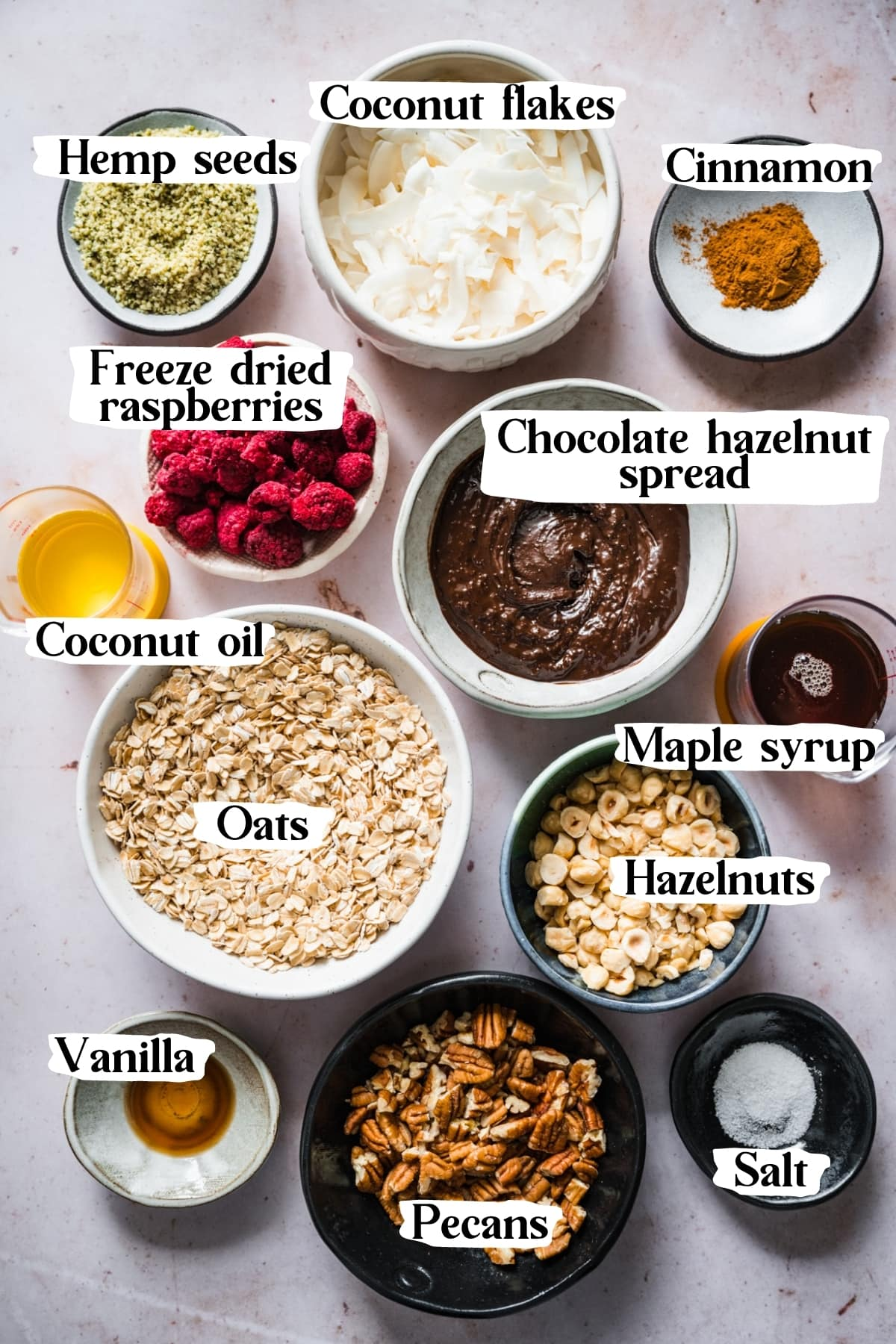 overhead view of ingredients for vegan chocolate hazelnut raspberry granola in small bowls.