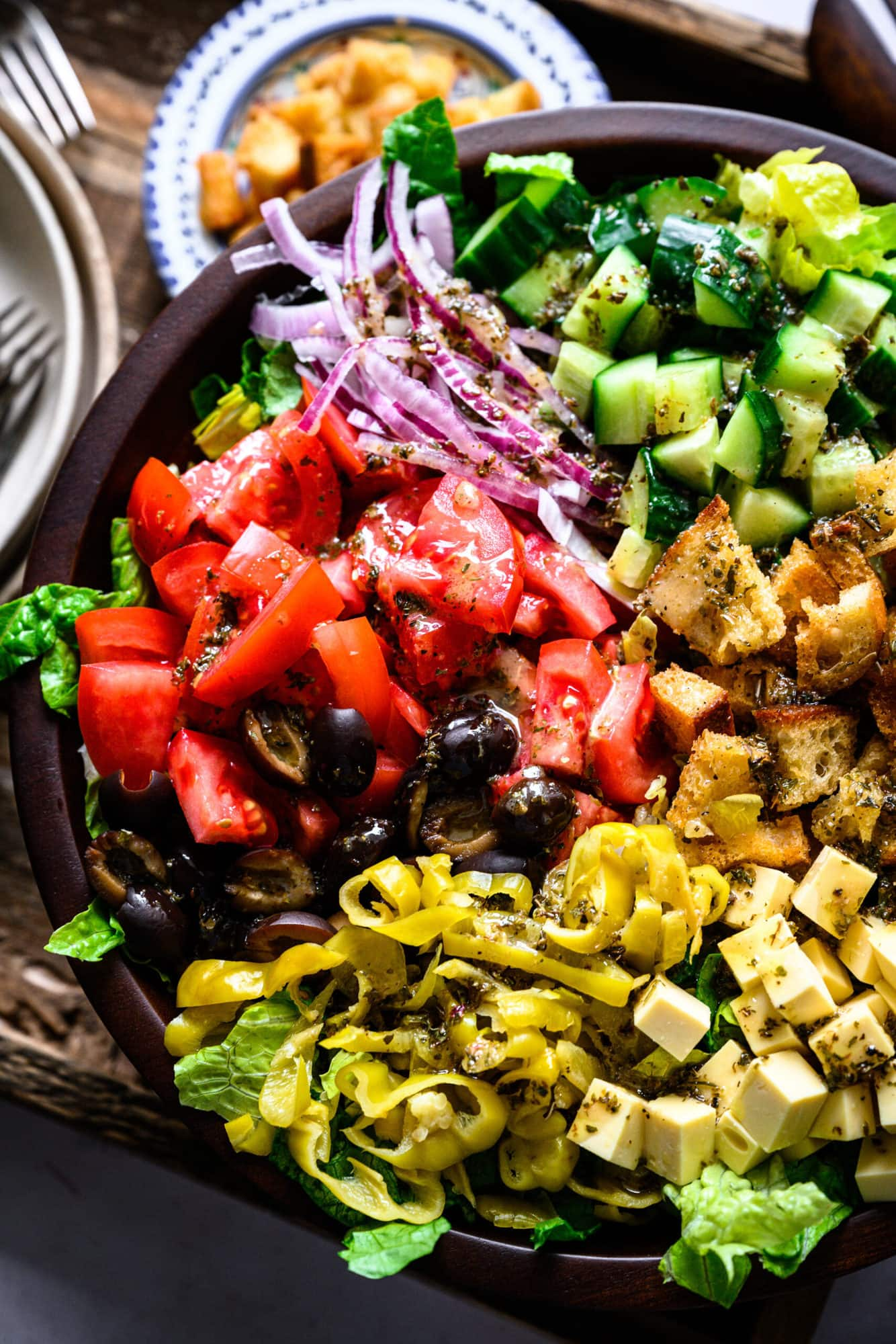 close up overhead view of vegan italian chopped salad in large wood salad bowl.