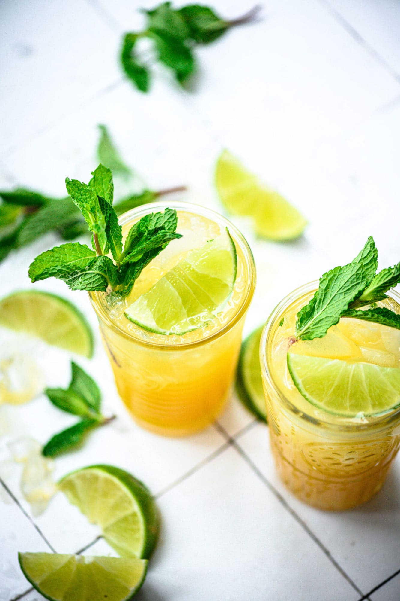 side view of mango mojitos in tall cocktail glasses garnished with mint and lime on white tile.