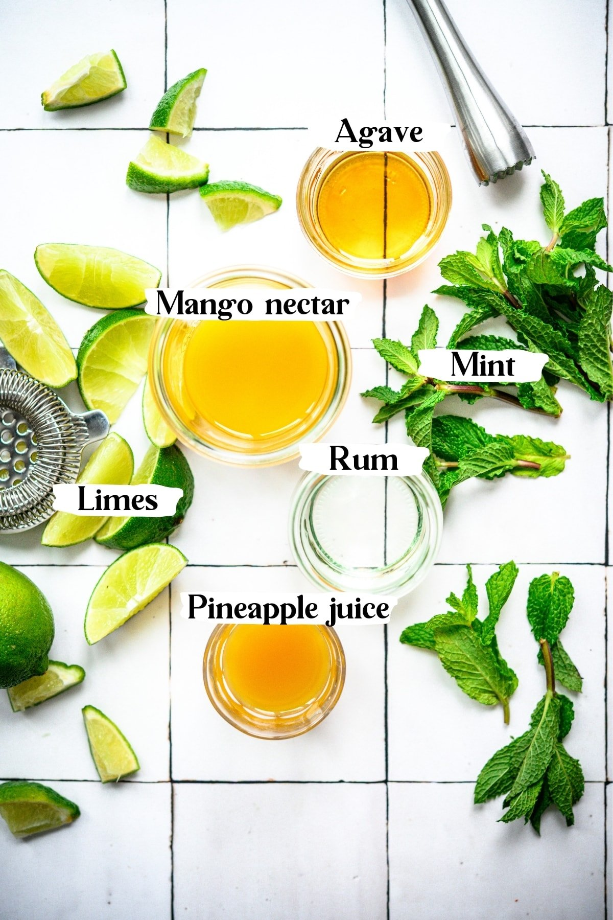 overhead view of mango nectar, rum, limes, mint, pineapple juice and agave in small bowls on white tile.