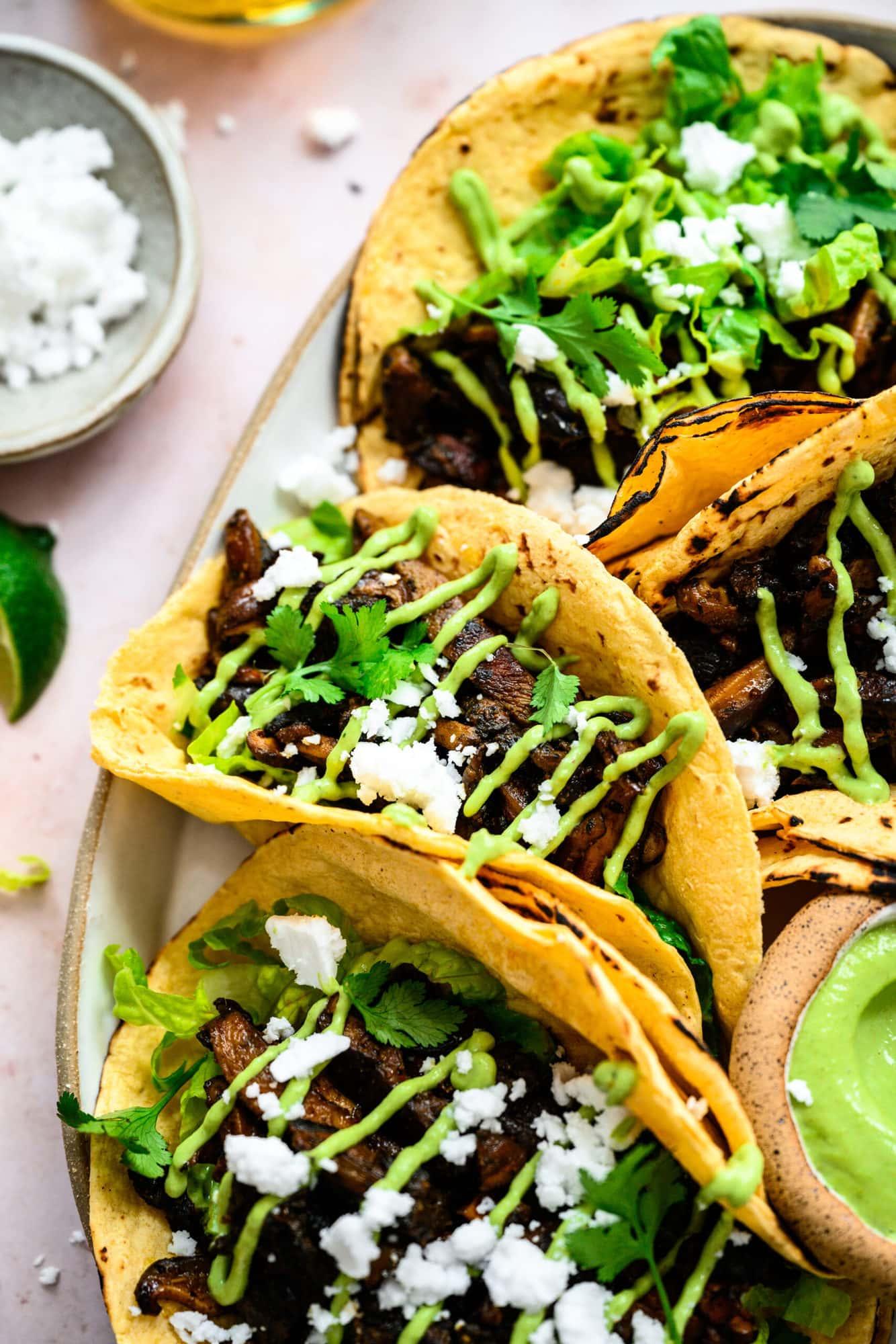 close up view of mushroom shawarma tacos on a platter with cilantro tahini sauce and feta.