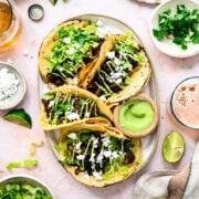 overhead view of mushroom shawarma tacos on a platter with cilantro tahini sauce and feta.