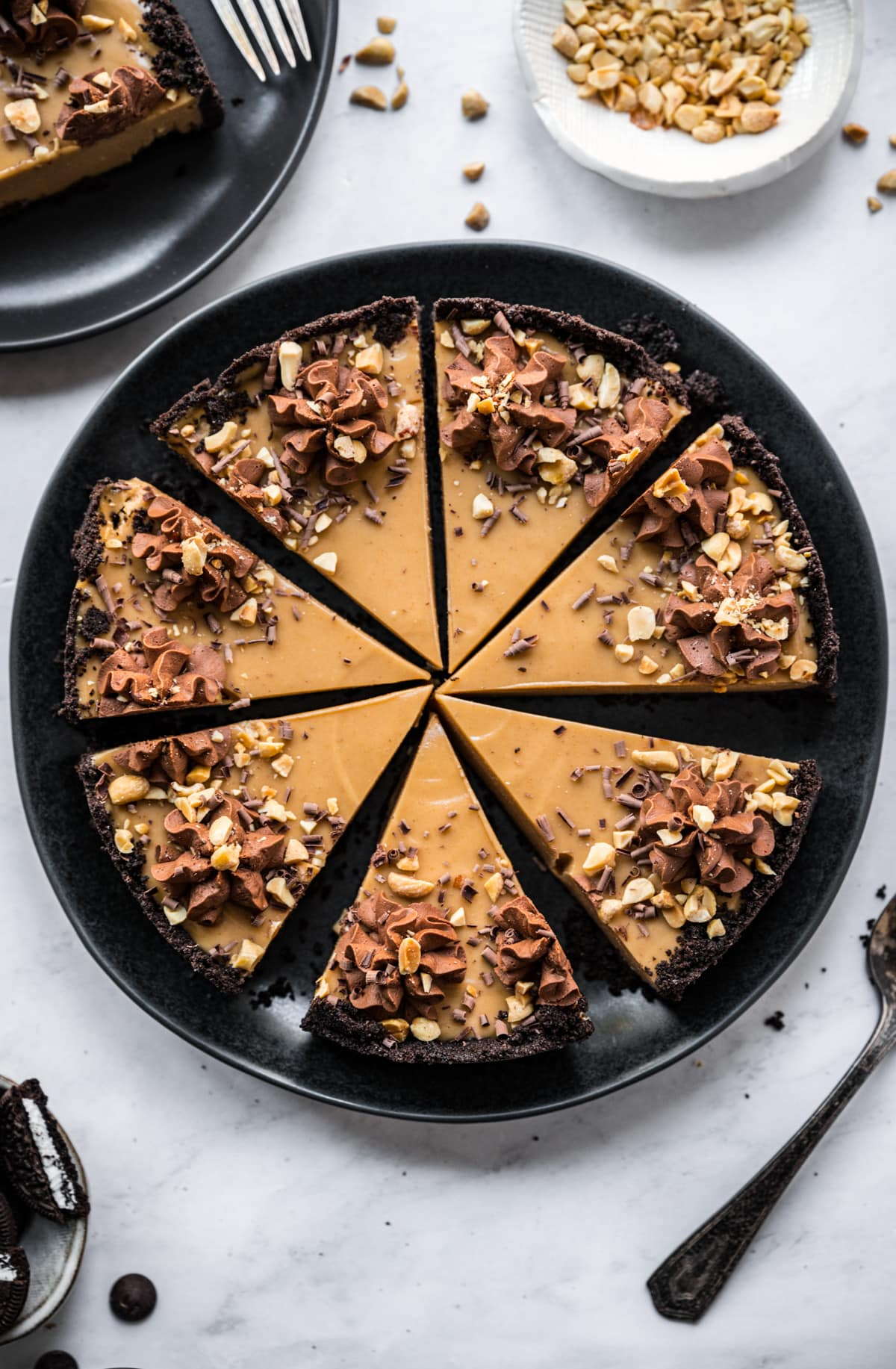 overhead view of peanut butter pie slices with chocolate cookie crust on black plate.