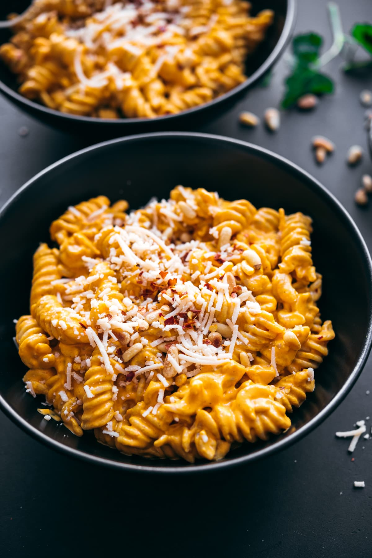 close up view of creamy vegan roasted red pepper pasta in black bowls topped with parmesan, pine nuts and red pepper flakes.