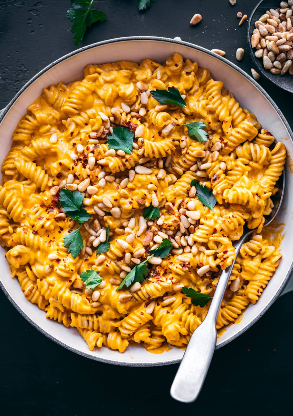 overhead view of creamy vegan roasted red pepper pasta in pan topped with pine nuts and red pepper flakes.