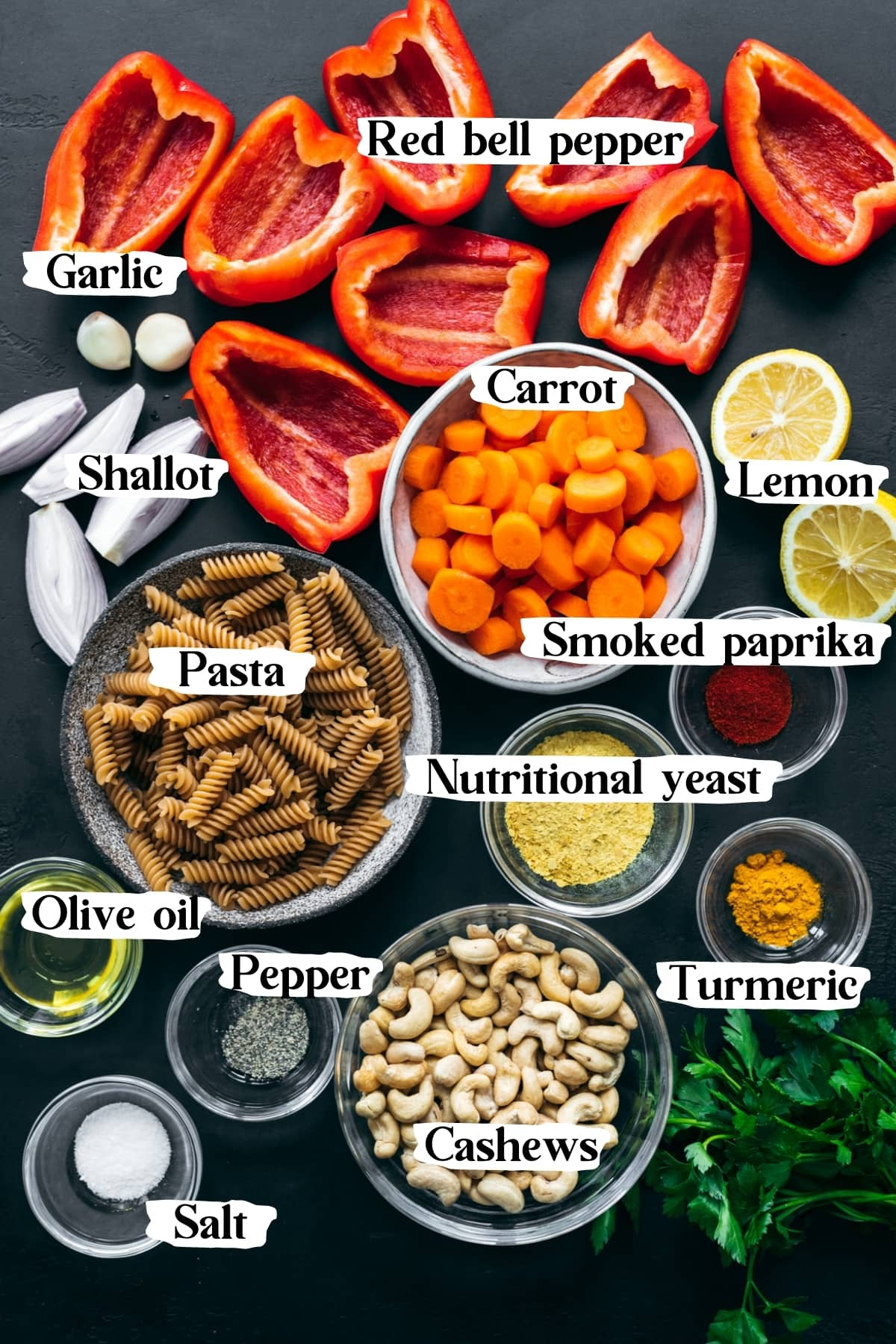 overhead view of ingredients for vegan roasted red pepper pasta in small bowls with text labels.