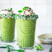 side view of two glasses of vegan shamrock shake with chocolate sprinkle rim and whipped cream on top.