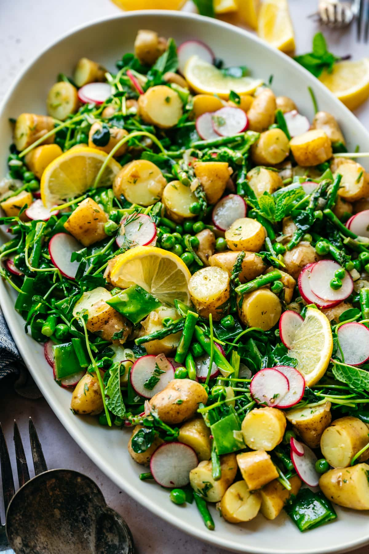 close up view of asparagus potato salad with peas and radishes on a large white platter.