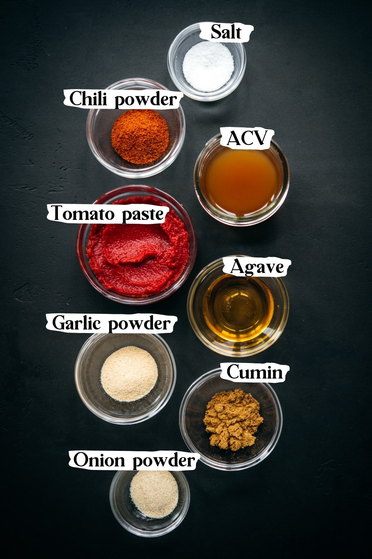 overhead view of ingredients and spices for homemade taco sauce in small glass bowls.