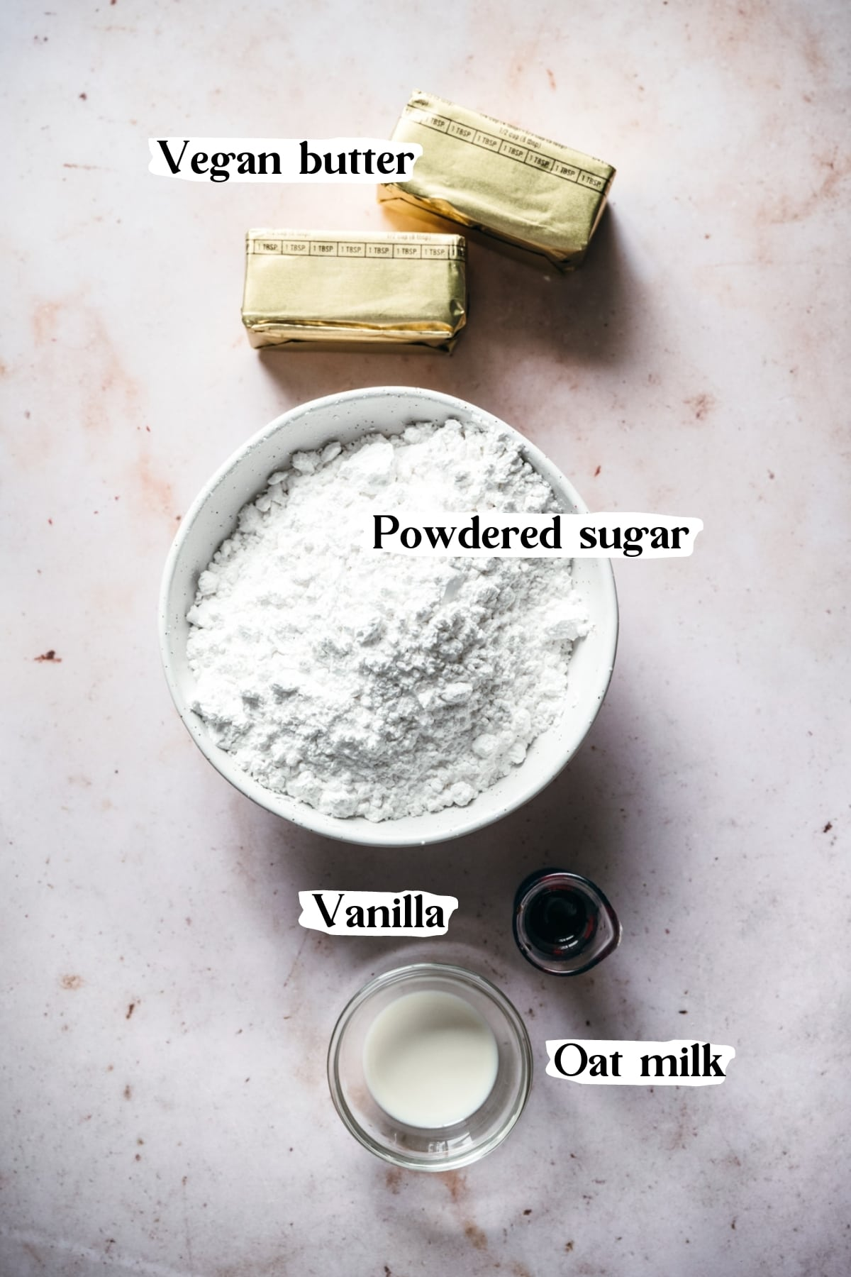 overhead view of ingredients to make vegan frosting, including vegan butter, powdered sugar, vanilla and milk.