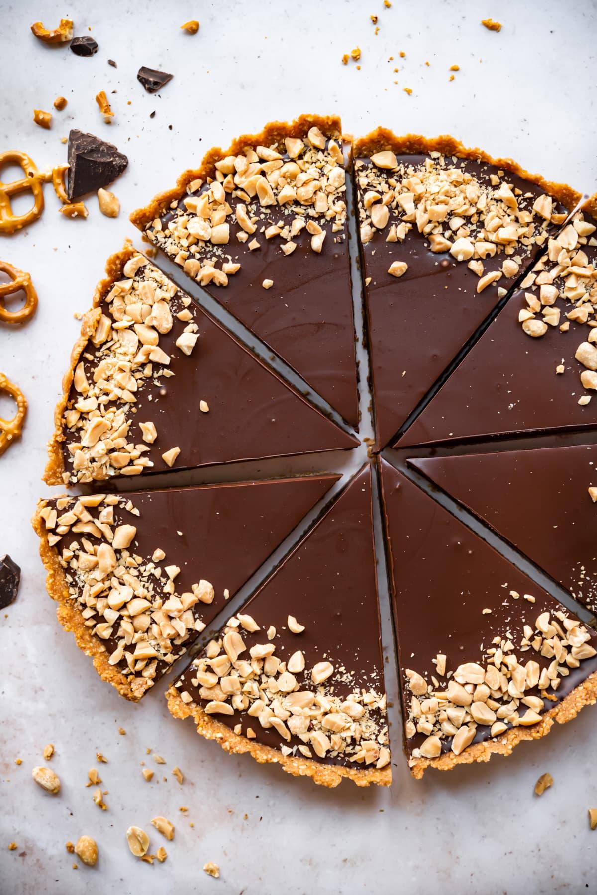 overhead view of chocolate peanut butter pretzel tart cut into slices.