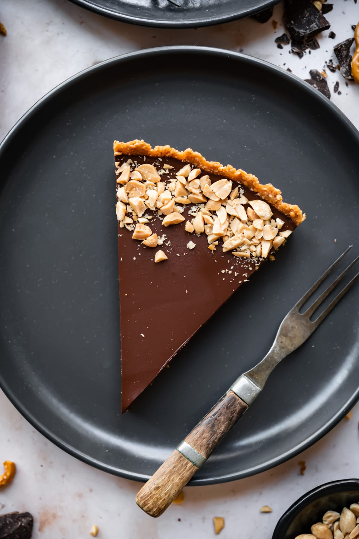 overhead view of slice of chocolate peanut butter pretzel tart on a black plate.