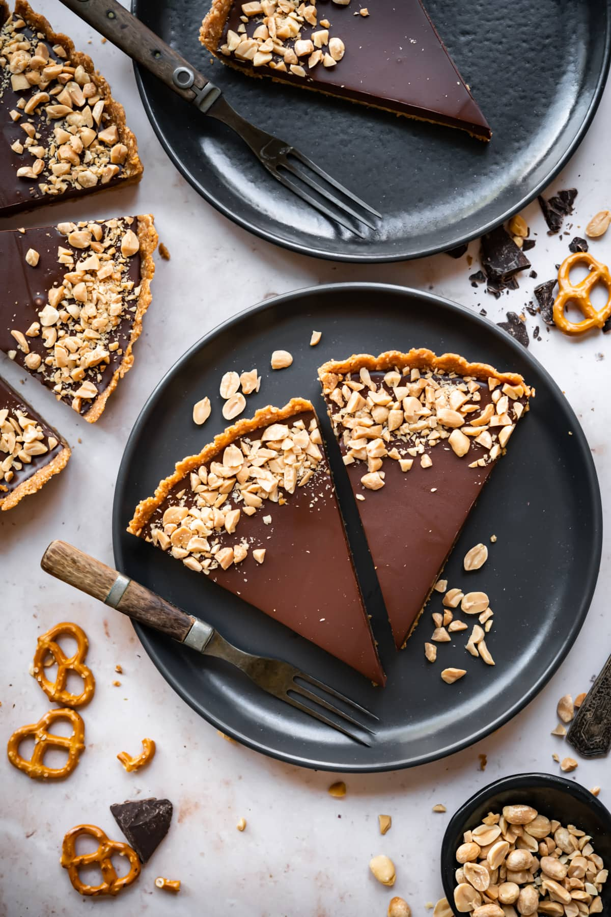 overhead view of 2 slices of chocolate peanut butter pretzel tart on a black plate.