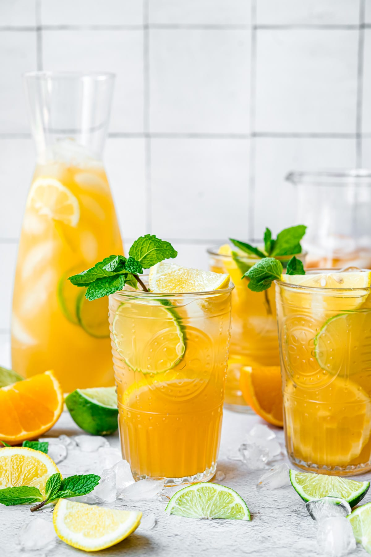Long island iced tea in two glasses served with sprigs of mint and wedges of lime and lemon.