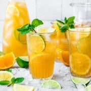 Two glasses of long island iced tea with mint, lemon and lime.