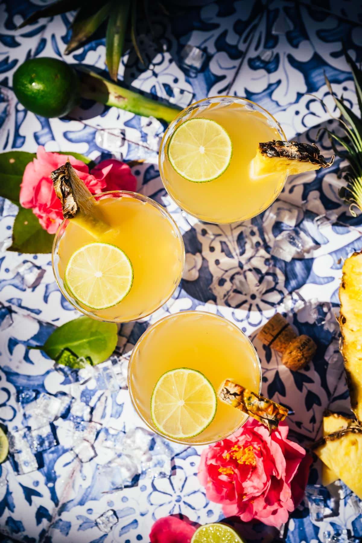 overhead view of pineapple mimosas on blue tile backdrop.