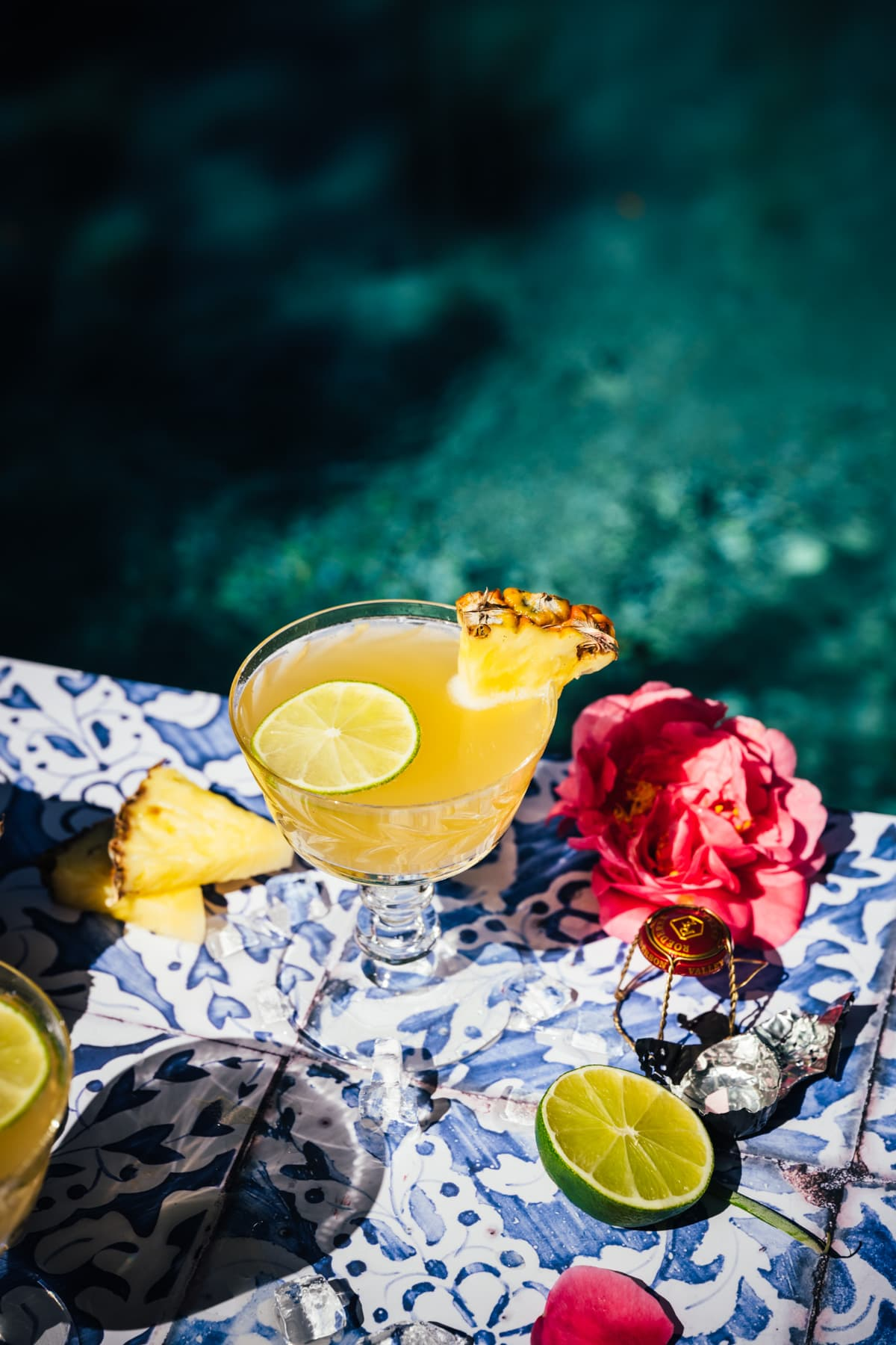 overhead view of pineapple mimosa on blue tile with pool in background.