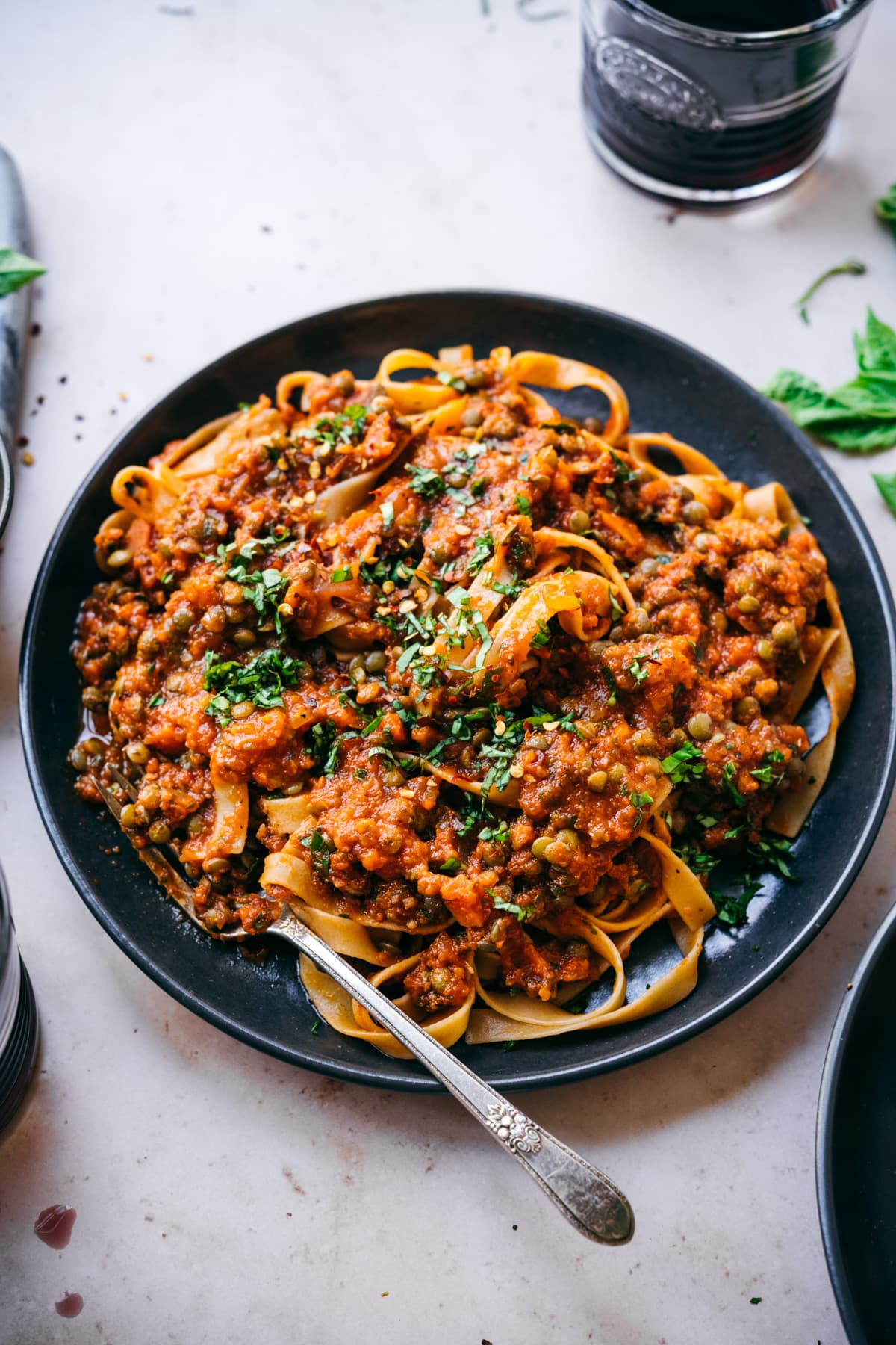 close up view of vegan lentil bolognese sauce over pasta on black plate with fork.