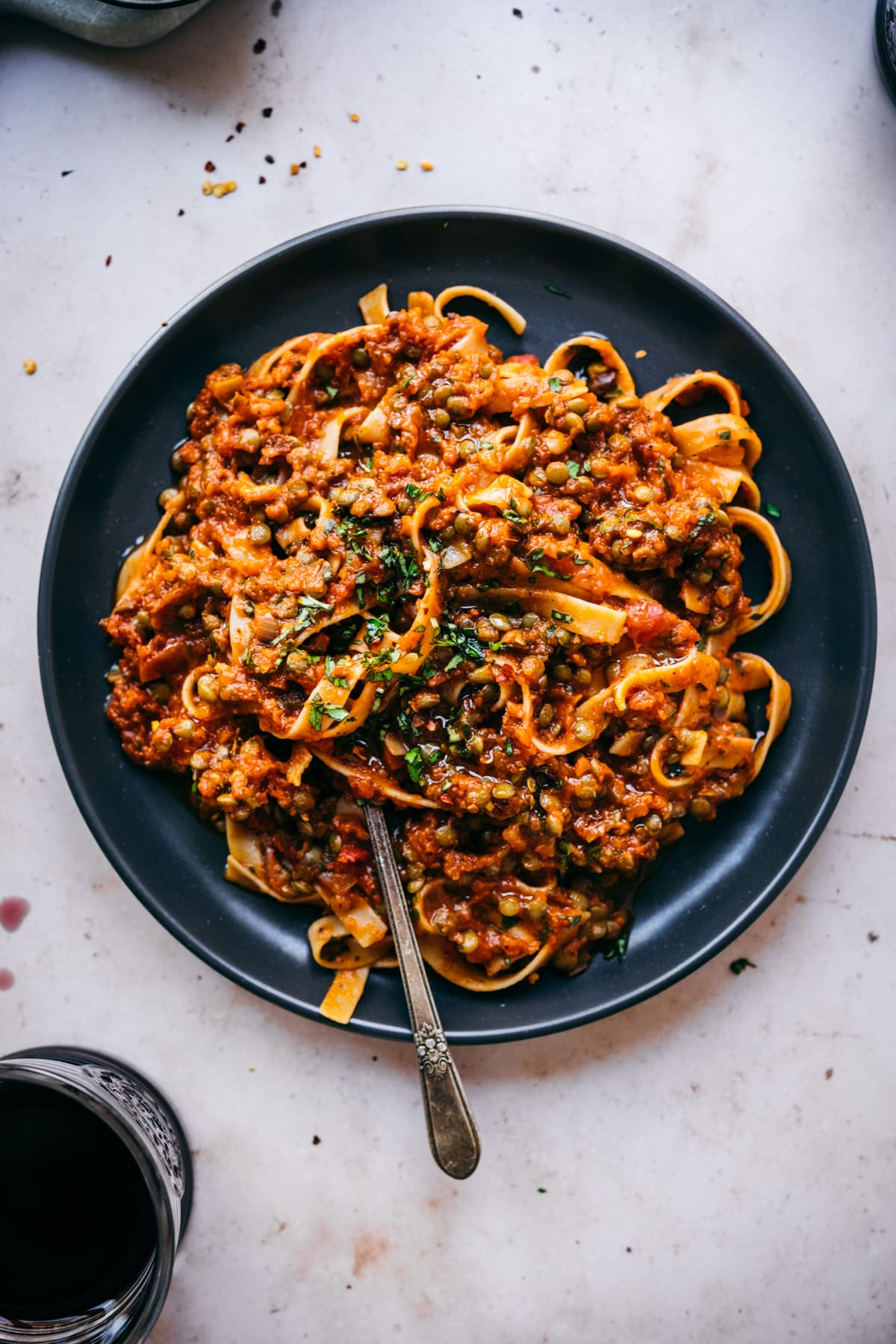 overhead view of vegan lentil bolognese sauce over pasta on black plate with fork.
