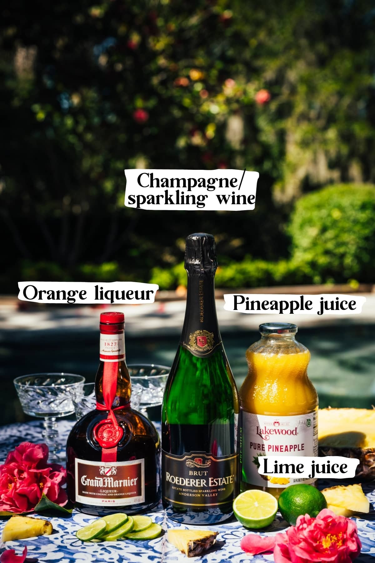 side view of ingredients for pineapple mimosas, including sparkling wine, pineapple juice, grand marnier and limes.