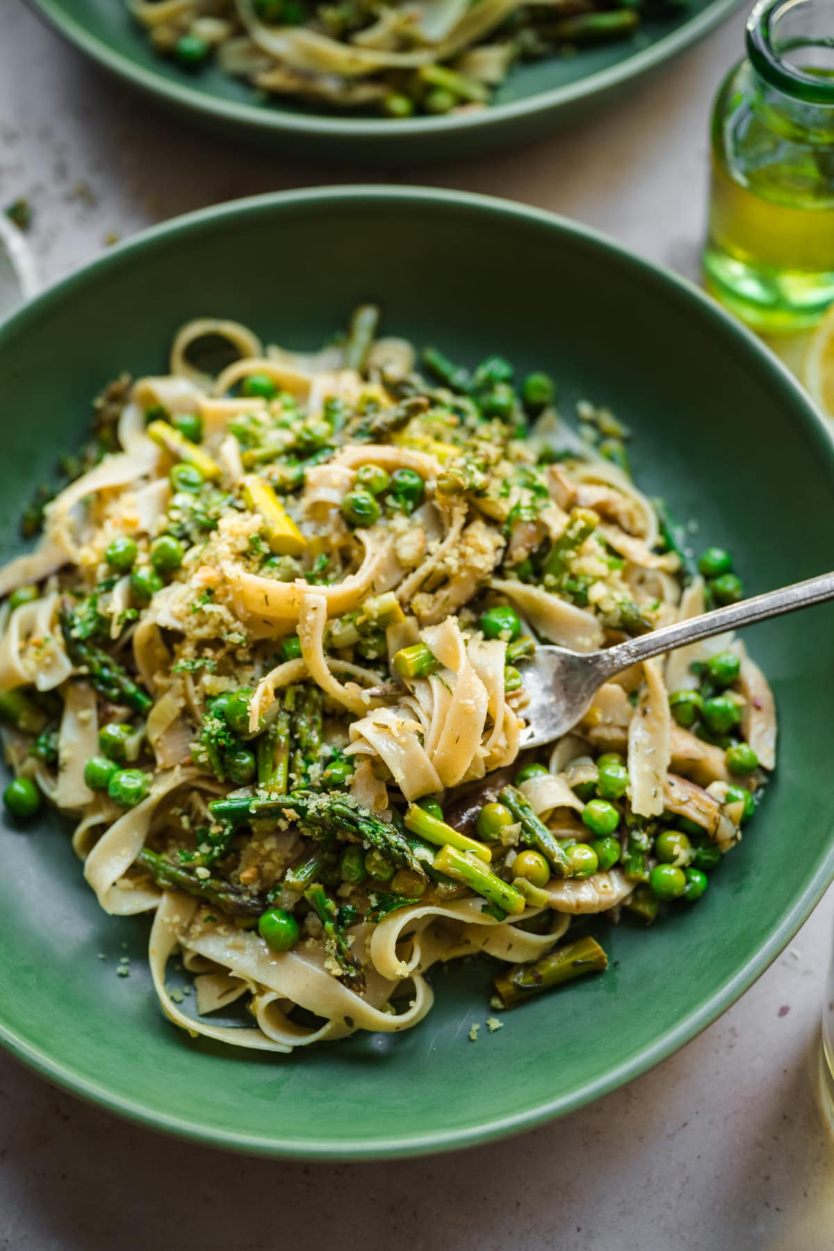 close up view of vegan spring vegetable pasta plated in a green bowl with breadcrumb topping.