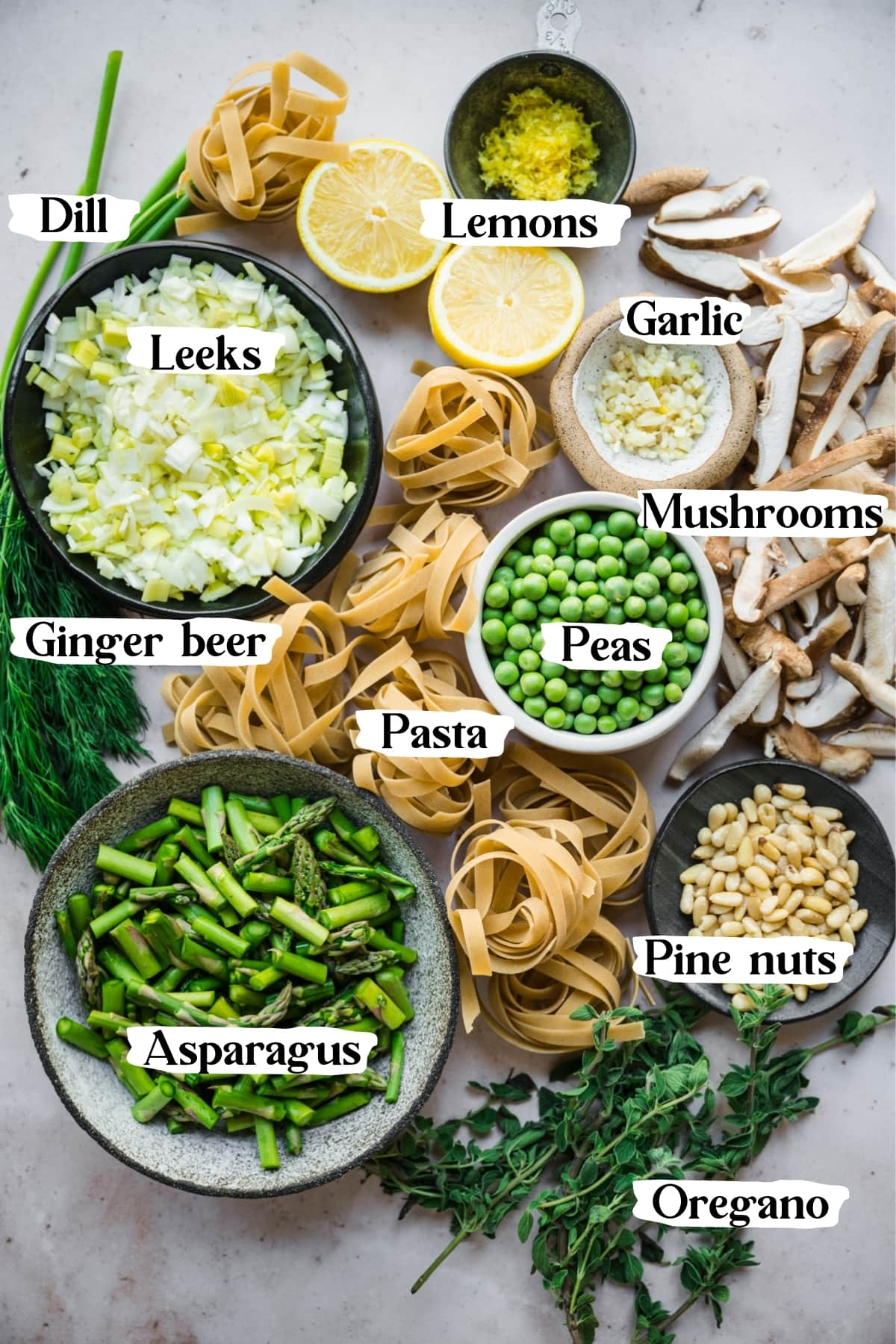 overhead view of ingredients for vegan spring vegetable pasta in small bowls with text labels.