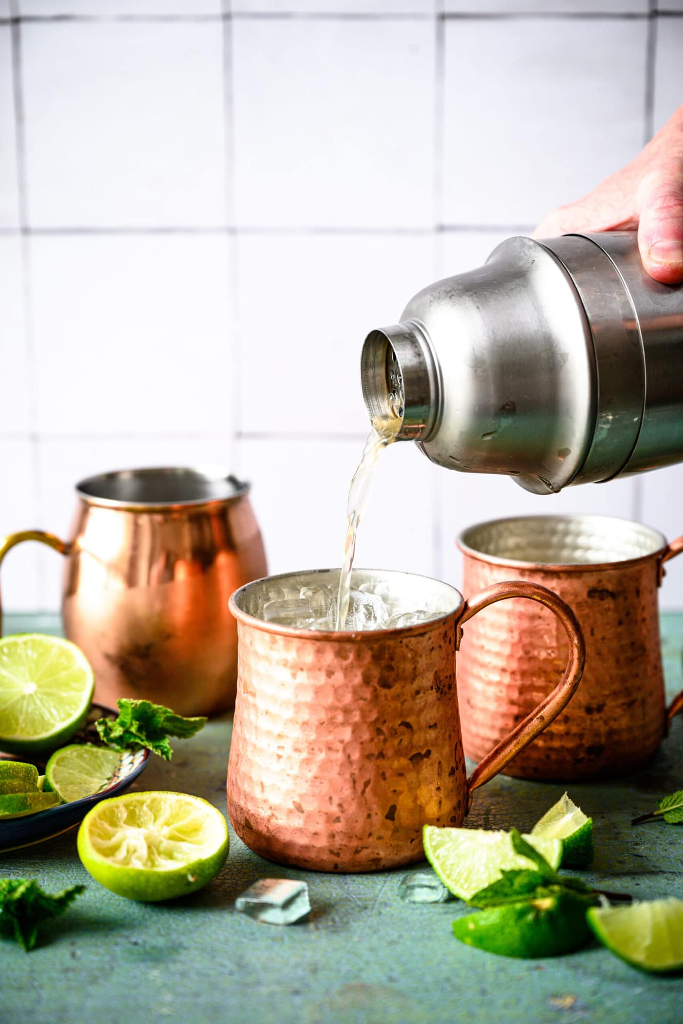 pouring tequila mule cocktail from cocktail shaker into copper mug filled with ice.