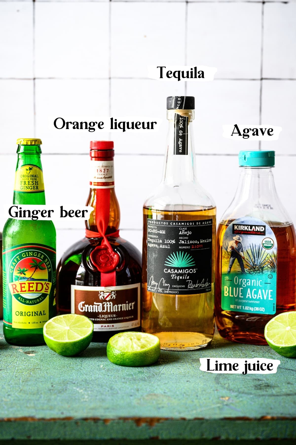 side view of ingredients for tequila mules, including ginger beer, tequila, Grand Marnier and agave.