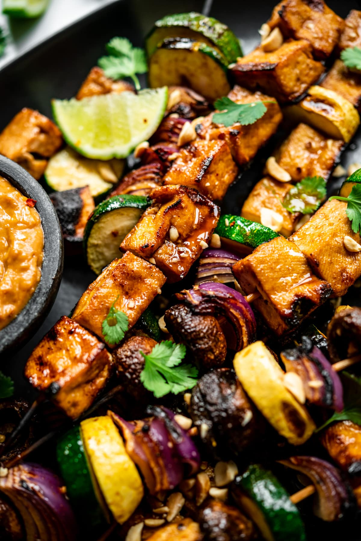 close up view of grilled tofu kebabs with vegetables on a platter.