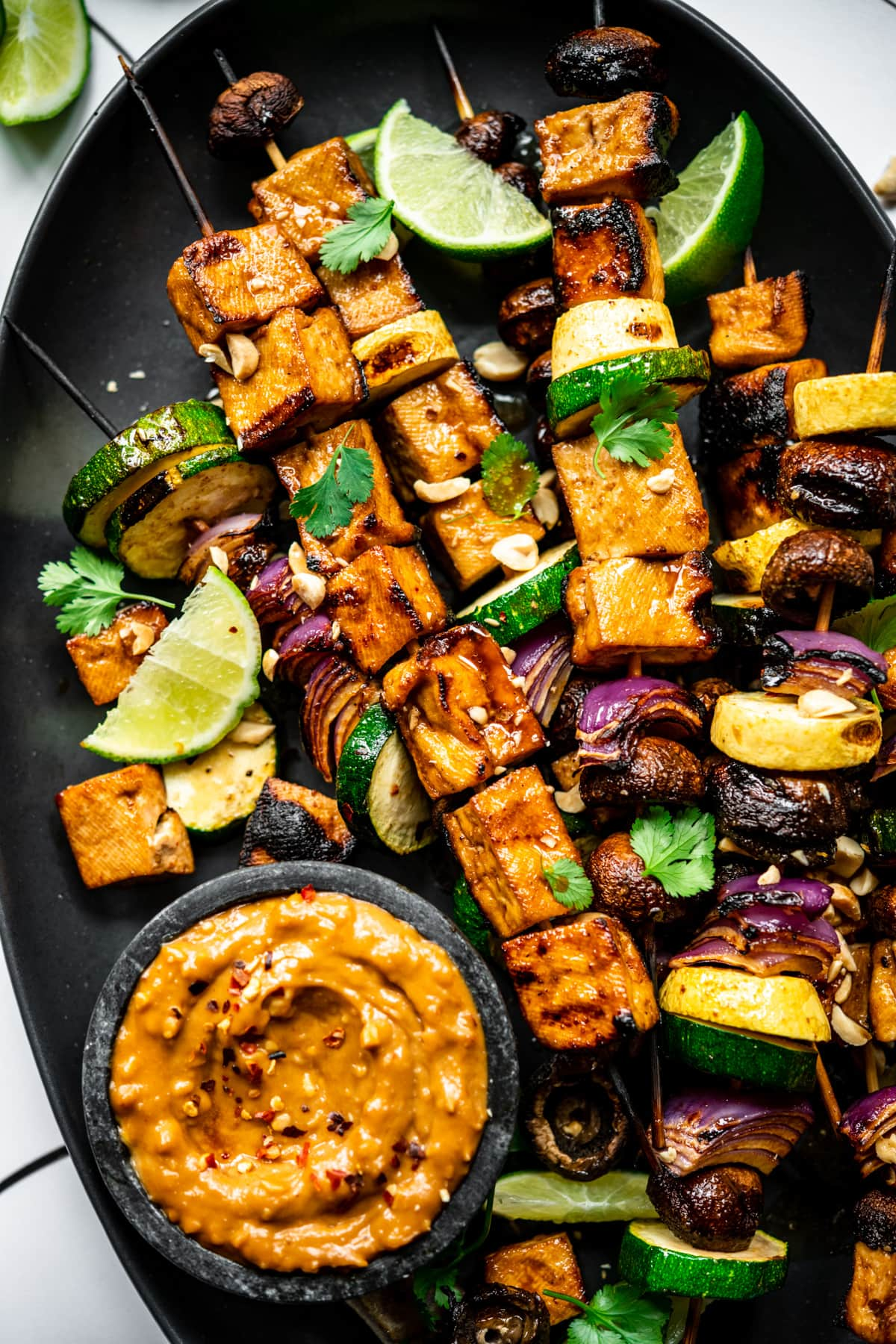 close up view of grilled tofu kebabs with vegetables on a platter with a bowl of peanut sauce.