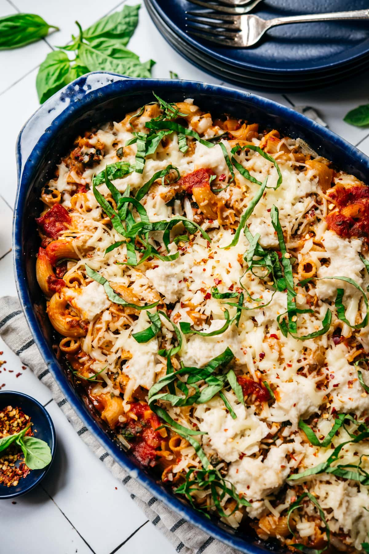 close up view of vegan pasta bake topped with cheese and basil in a blue baking dish.