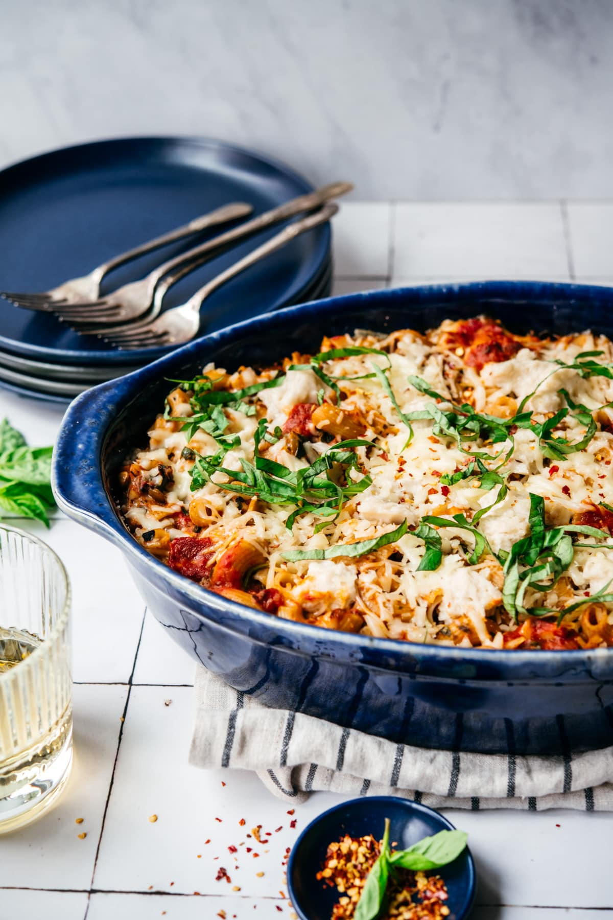 side view of vegan pasta bake topped with cheese and basil in a blue baking dish.