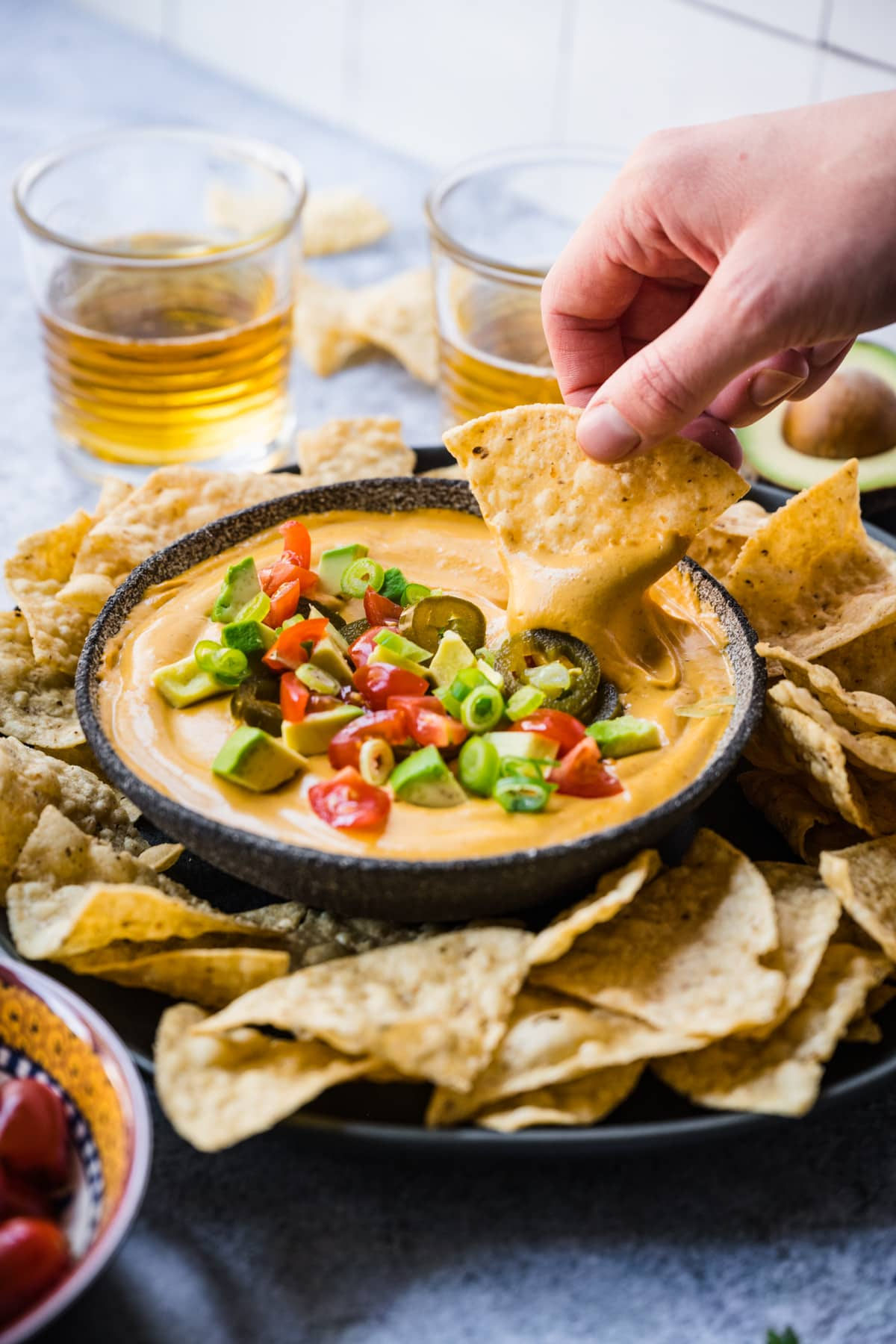 person dipping tortilla chip into vegan queso dip.
