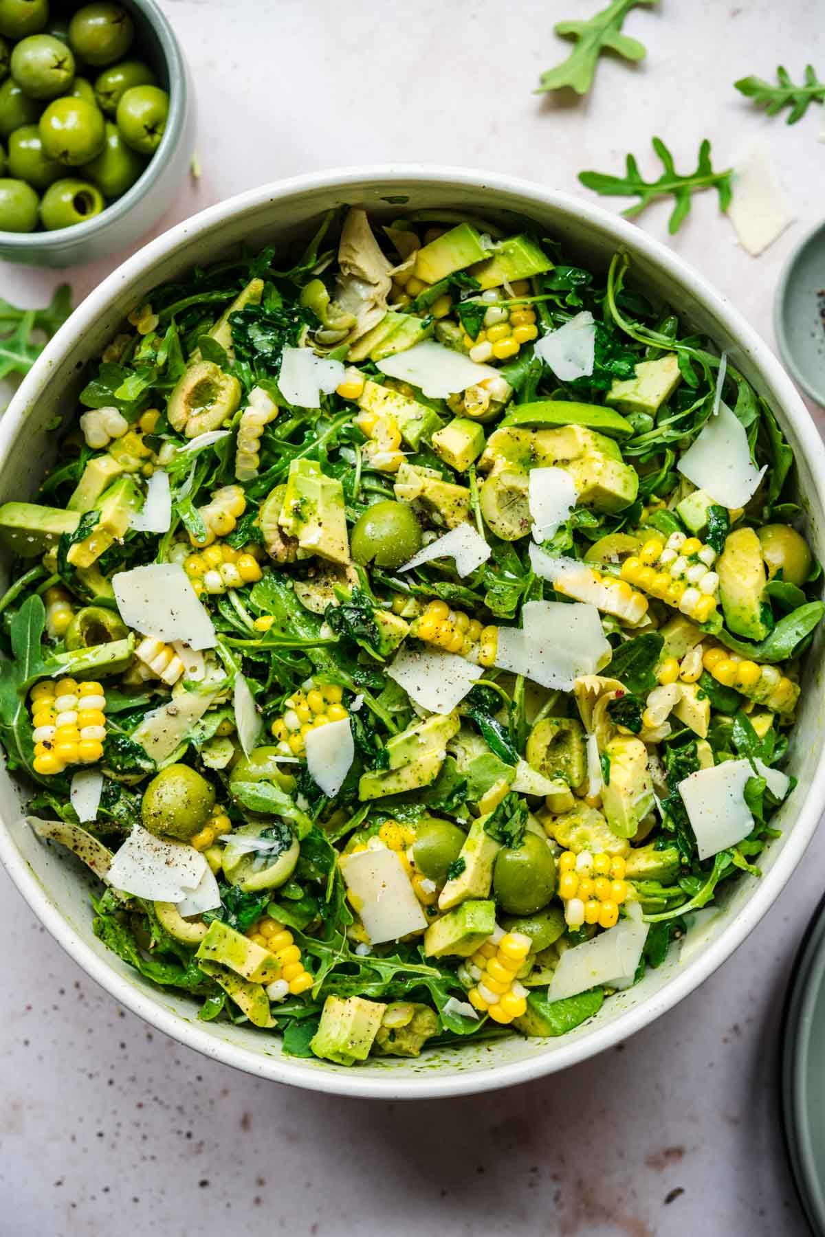close up overhead view of corn avocado arugula salad with basil dressing in large bowl.