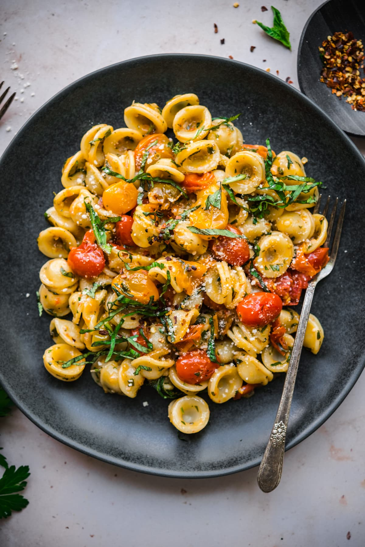 overhead view of burst cherry tomato pasta with fresh basil and red pepper flakes on black plate.