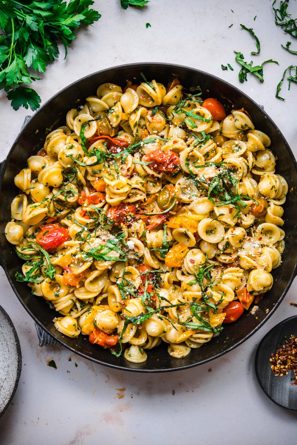 overhead view of burst cherry tomato pasta with fresh basil and red pepper flakes in skillet.