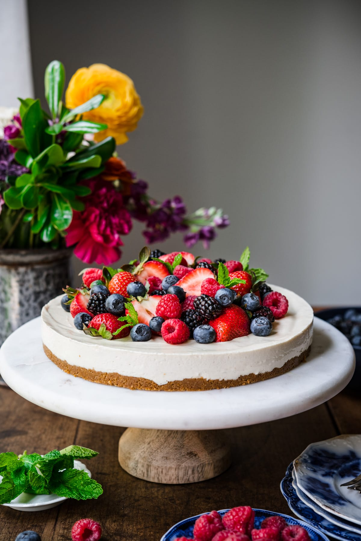 side view of no bake vegan cheesecake topped with fresh berries on a marble cake stand.
