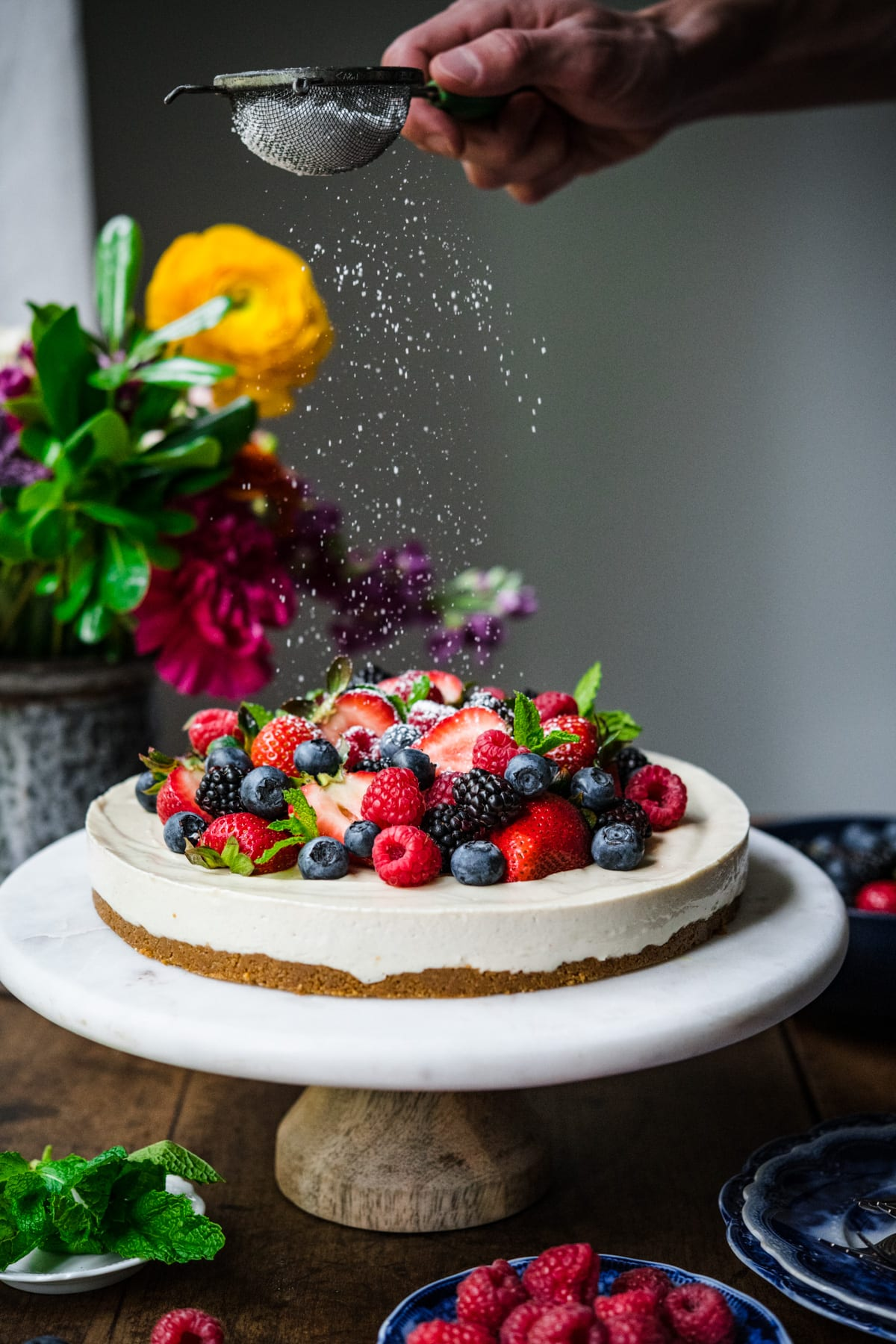 dusting powdered sugar onto no bake vegan cheesecake topped with fresh berries on a marble cake stand.