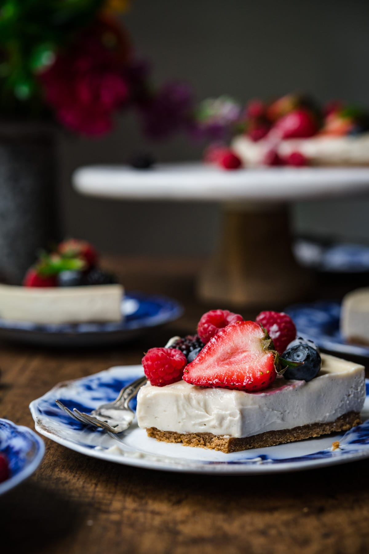 close up side view of slice of vegan no bake cheesecake on a blue china plate with fresh berries.