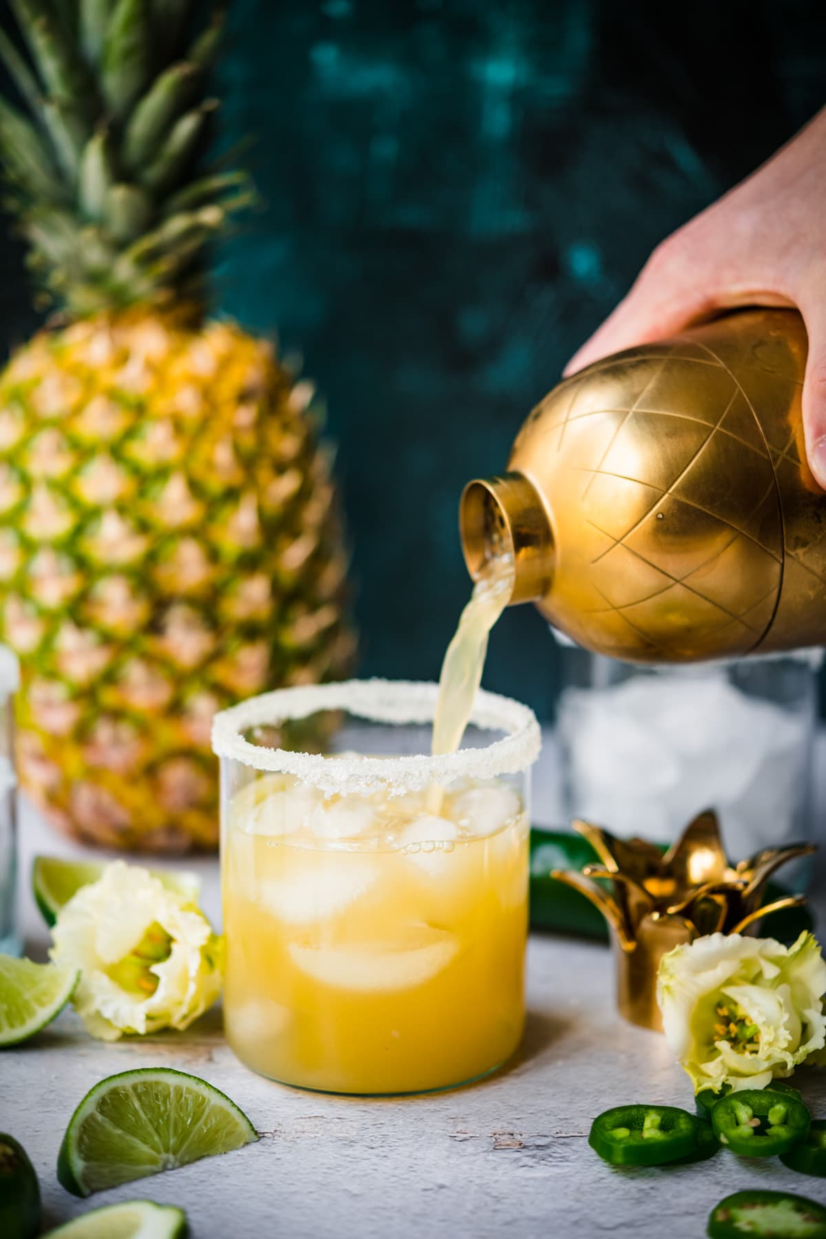 pouring pineapple jalapeño margarita from cocktail shaker into glass with salt rim and ice.