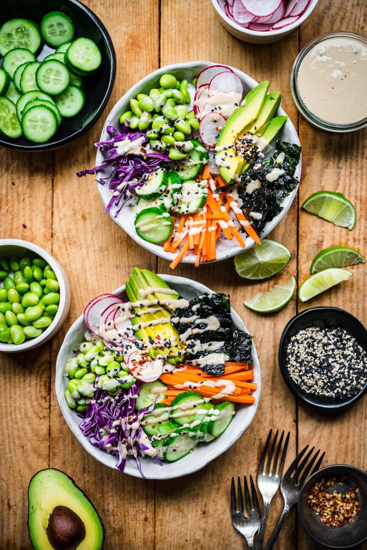 overhead view of vegan sushi bowls with avocado, radishes, cucumber, edamame and miso tahini dressing.