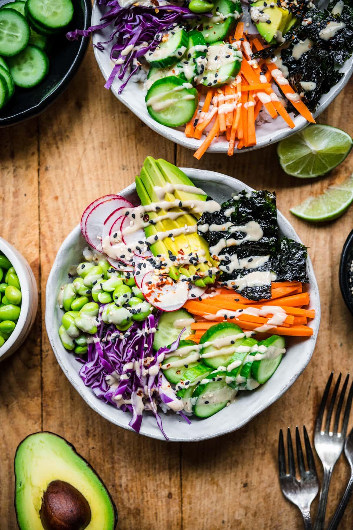 overhead view of vegan sushi bowl with avocado, radishes, cucumber, edamame and miso tahini dressing.