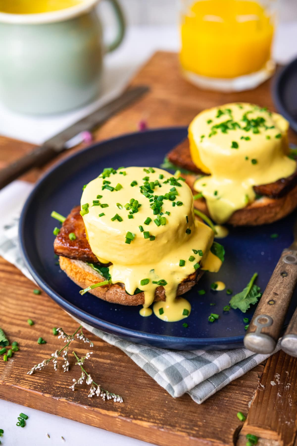side view of vegan eggs benedict on a blue plate with hollandaise sauce and chives.