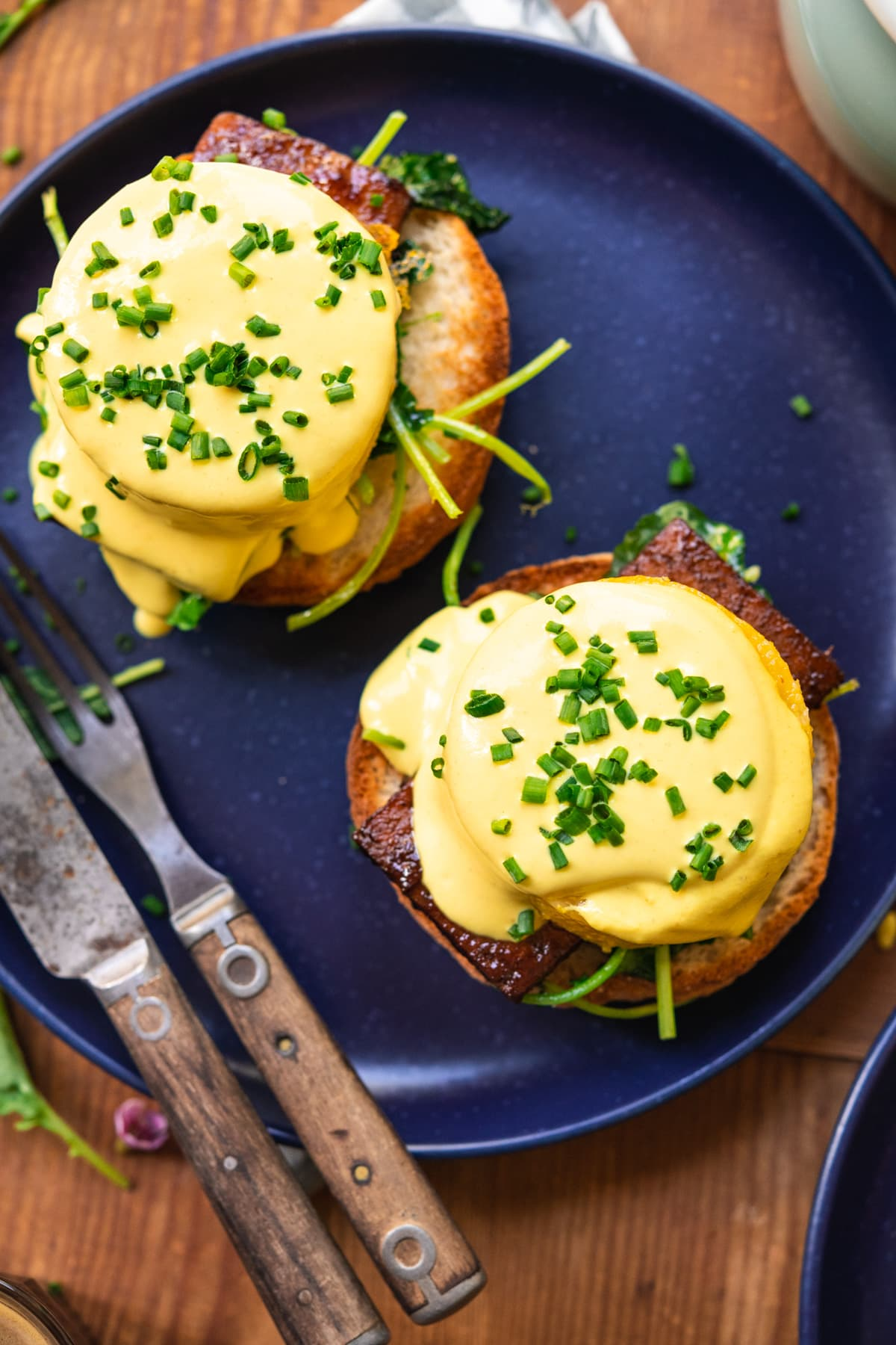 overhead view of vegan eggs benedict on a blue plate with hollandaise sauce and chives.