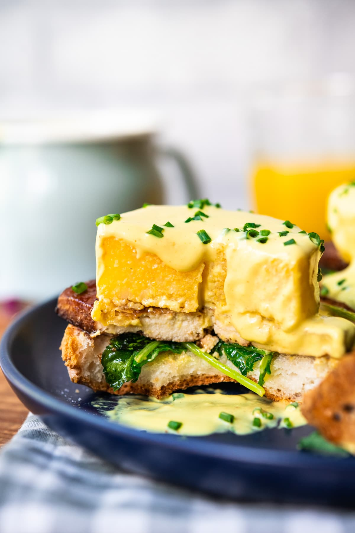 close up side view of cross section of polenta eggs benedict with vegan hollandaise sauce.